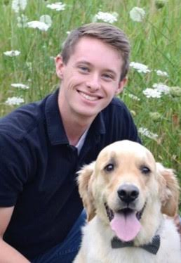Senior Honors College student Alex Hyde, posing for photo with dog.