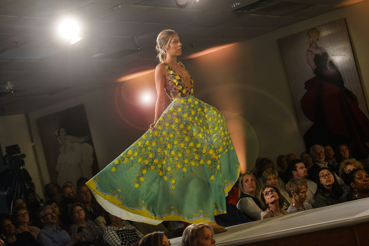 A model walks on the runway sporting a green and yellow gown during Kent State University's 2018 Annual Fashion Show.