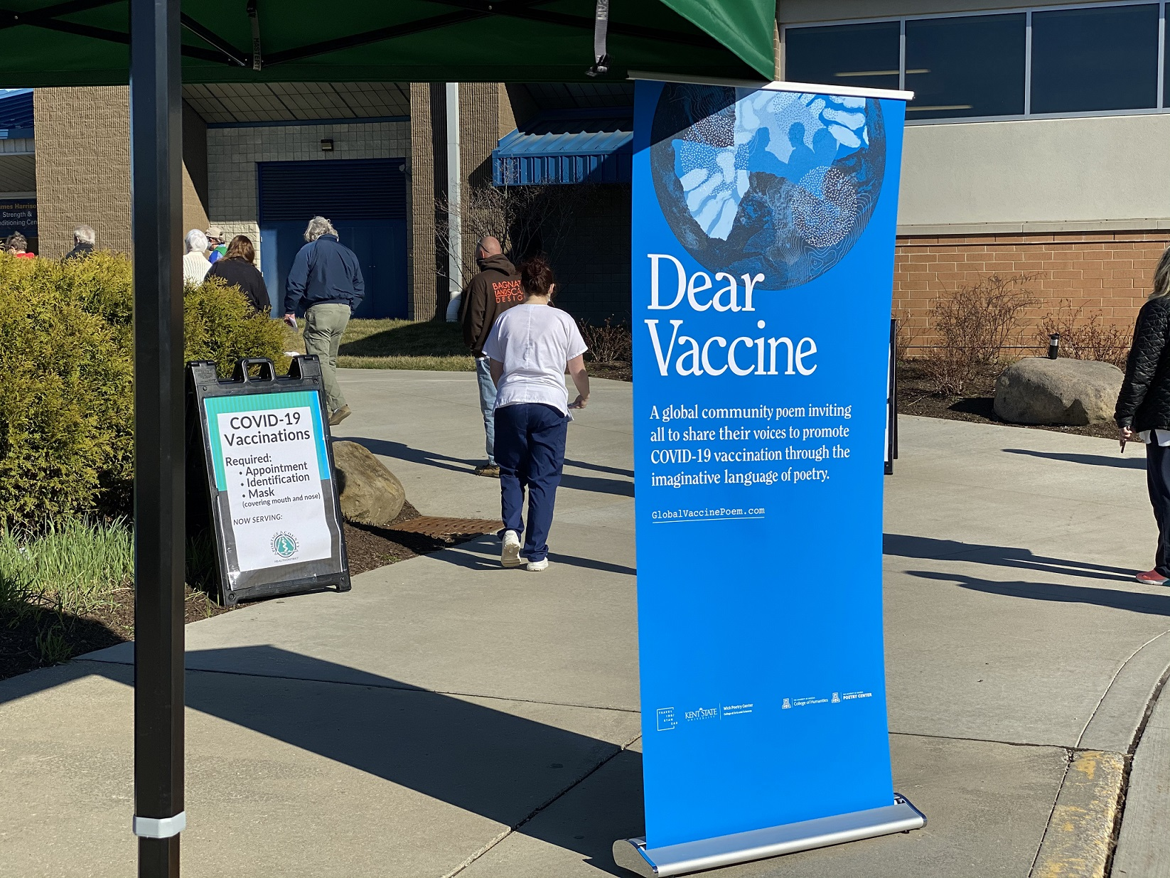 A banner promoting the Global Vaccine Poem project stands outside the Kent State University Field House during a mass COVID-19 vaccination event.