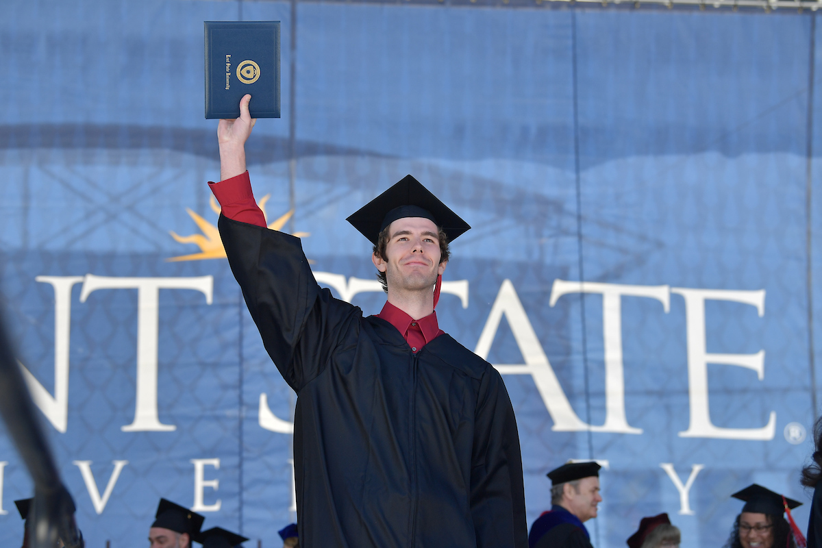 A new graduate of Kent State University triumphantly raises his diploma during the One University Commencement last year.