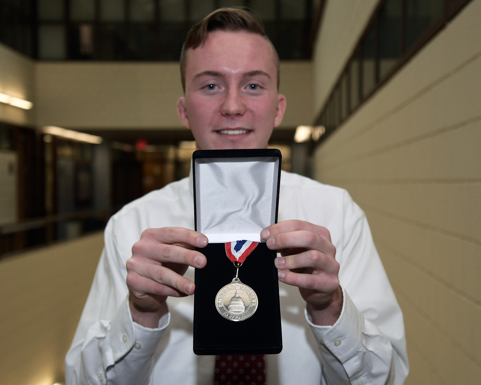 Kent State student Austin Croft displays the Congressional Award Silver Medal following a ceremony in Henderson Hall, home of the College of Nursing at Kent State.