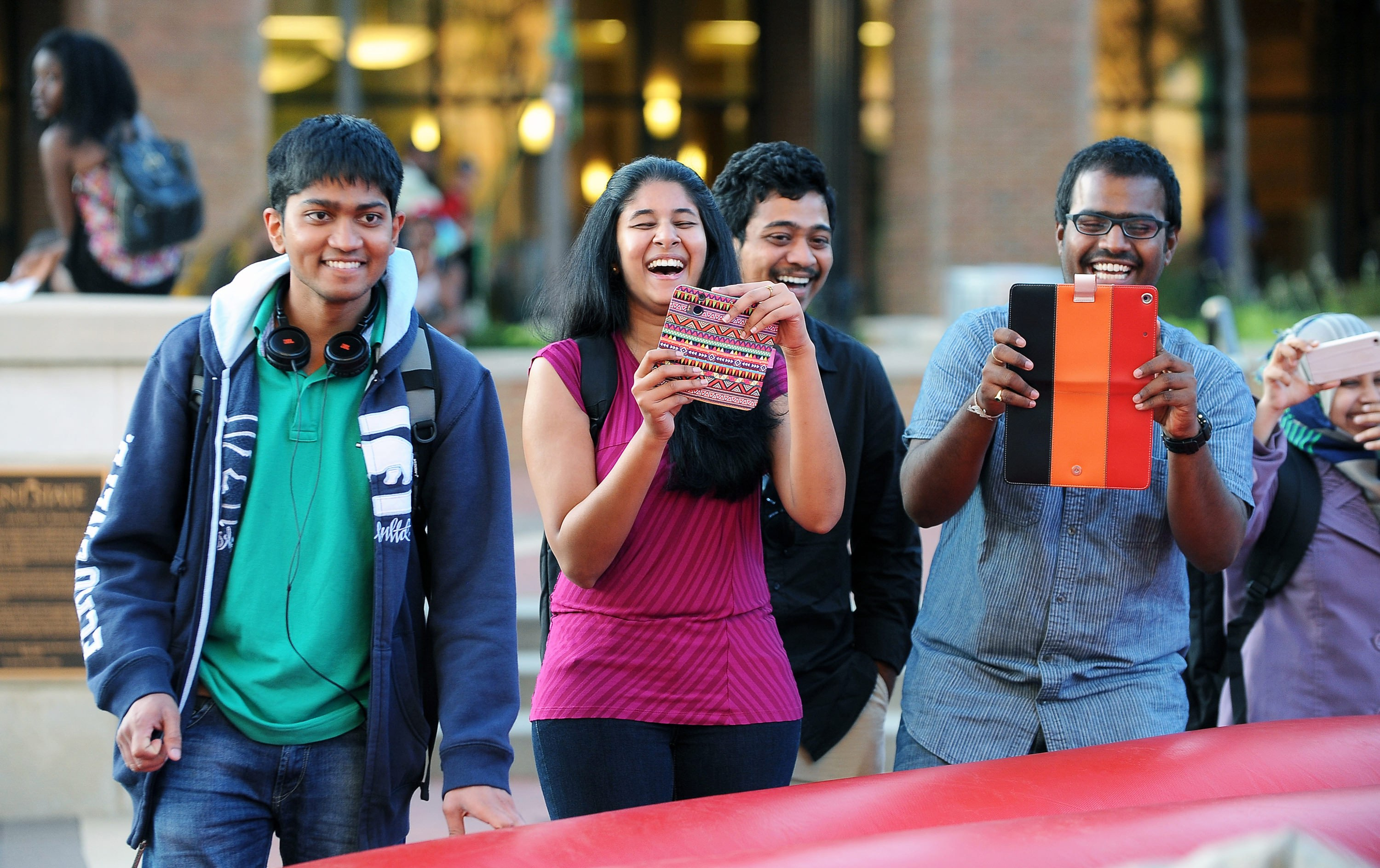 International students laughing with iPads and cell phones