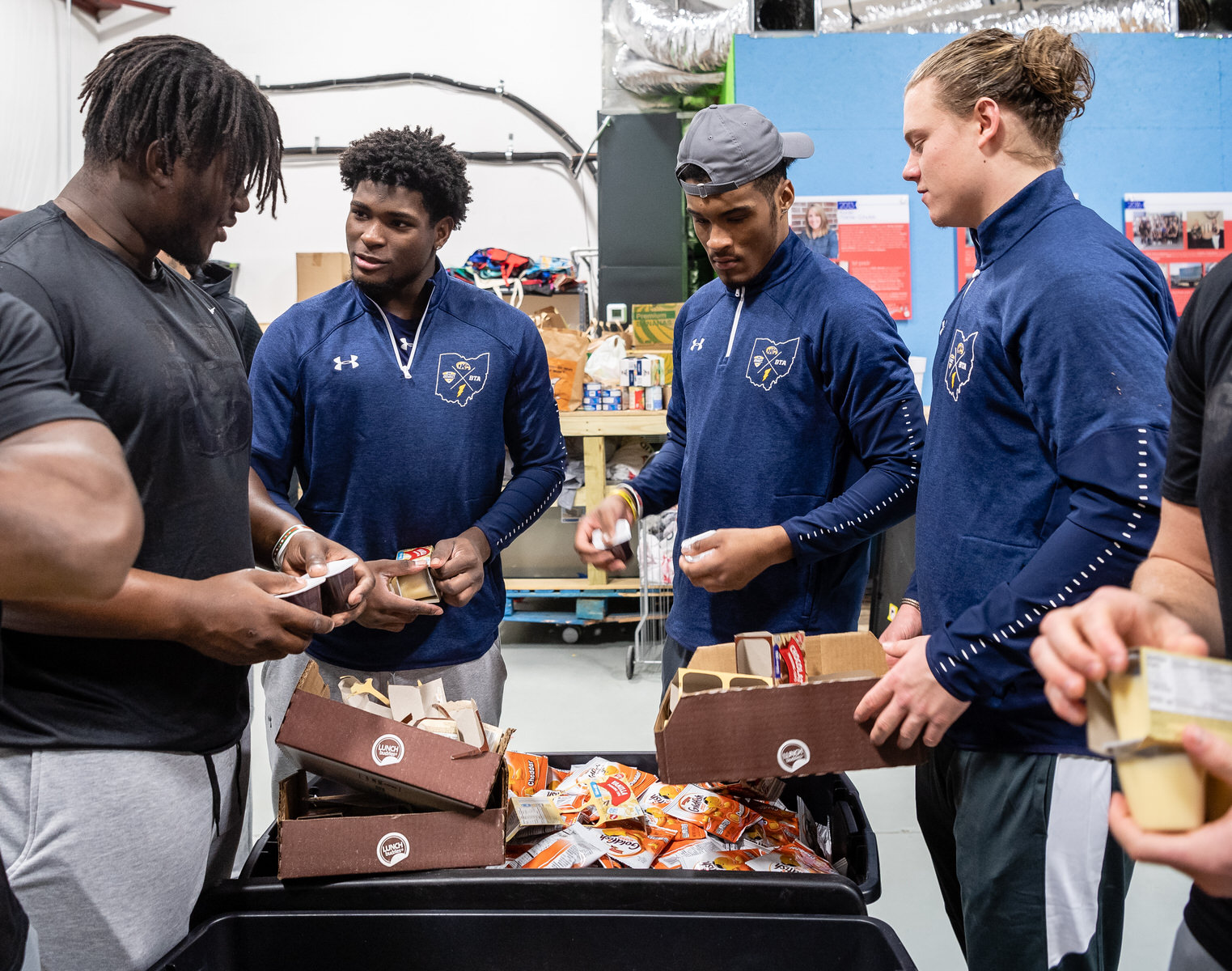 Kent State football players prepare meals for needy children ahead of the Tropical Smoothie Cafe Frisco Bowl.