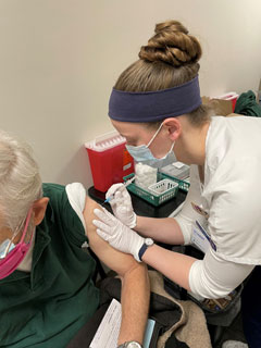 Melody Troyer, a BSN student from the Salem Campus, administers a COVID-19 vaccine to a community member.
