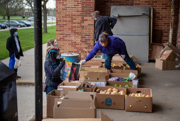 Cassie Pegg-Kirby, director of the Women's Center at Kent State, distributes donated food on the loading dock at Beall Hall where it will be given to local families who find themselves in need during the COVID-19 crisis.