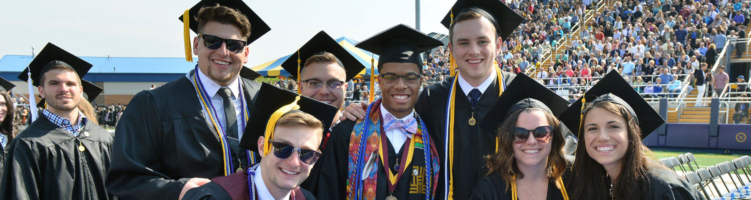 Photo of Kent State graduates, in graduation regalia, posed and smiling for the camera