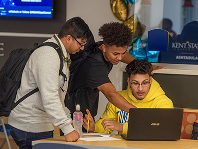 Photo of students, gathered together working on a laptop