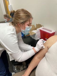 BSN student Kellie Walker injects a community member with the COVID-19 vaccine.