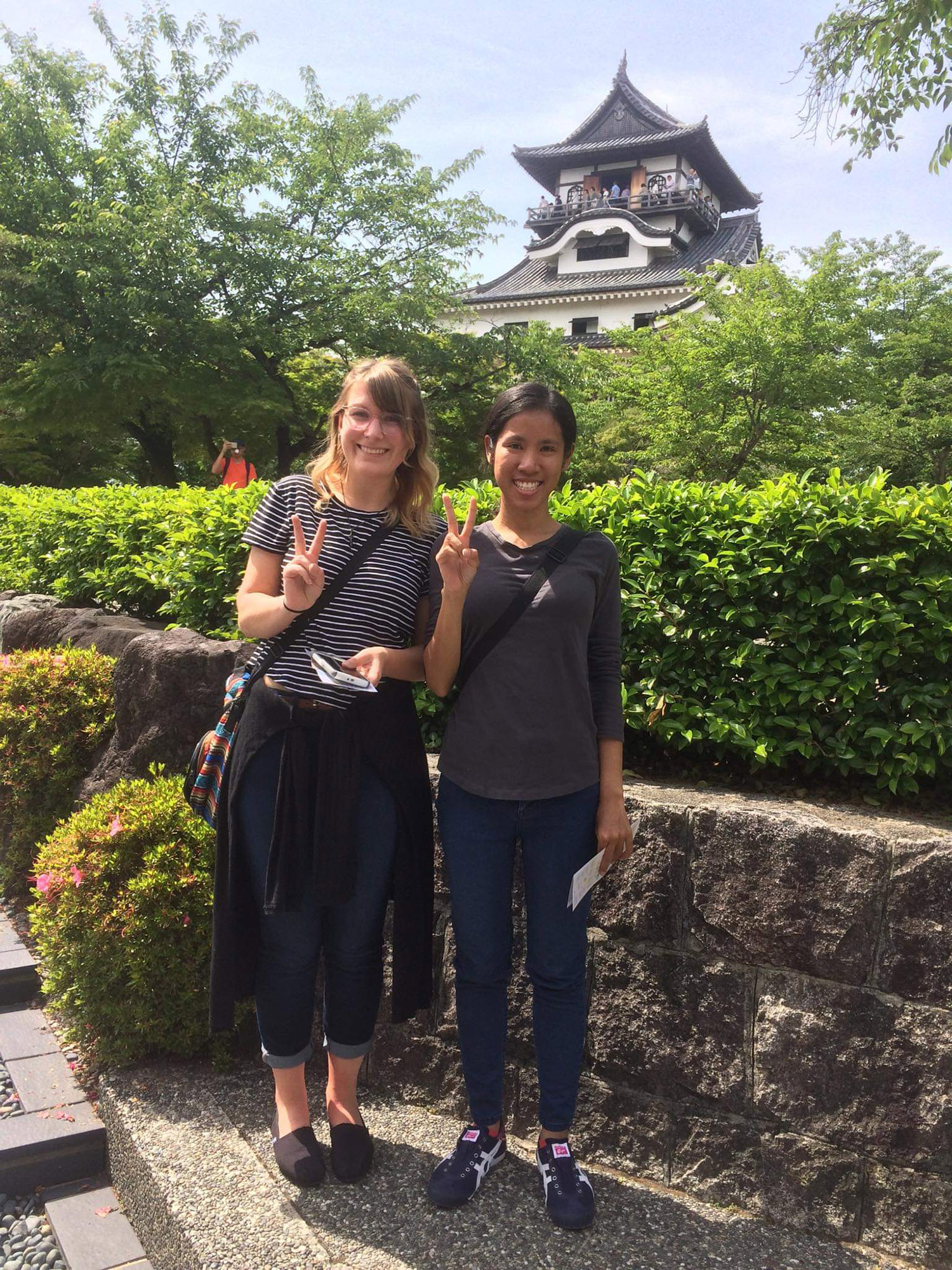 Two students, posed and smiling in front of the Inuyama Castle on a sunny day