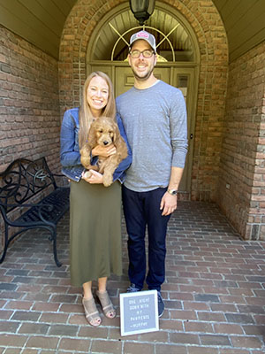 Adam and Amanda, holding their dog, posed for the camera
