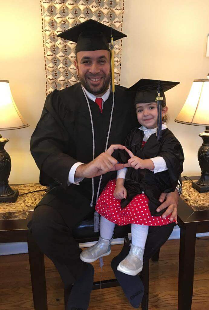 Graduate with daughter in cap and gown