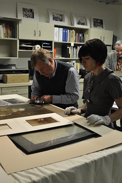 Alex Coon working with a conservationist looking at photo portraits on a table for an exhibition.