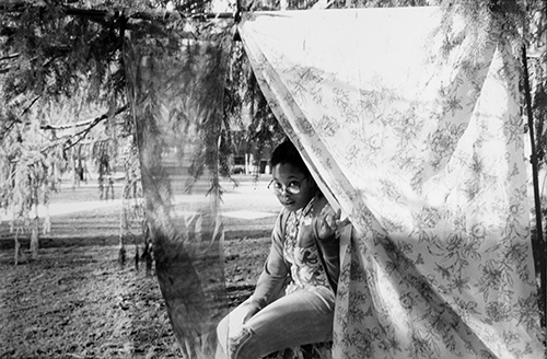 Black and white photograph of a person peering from behind a hanging bedsheet by student Amber Bishop