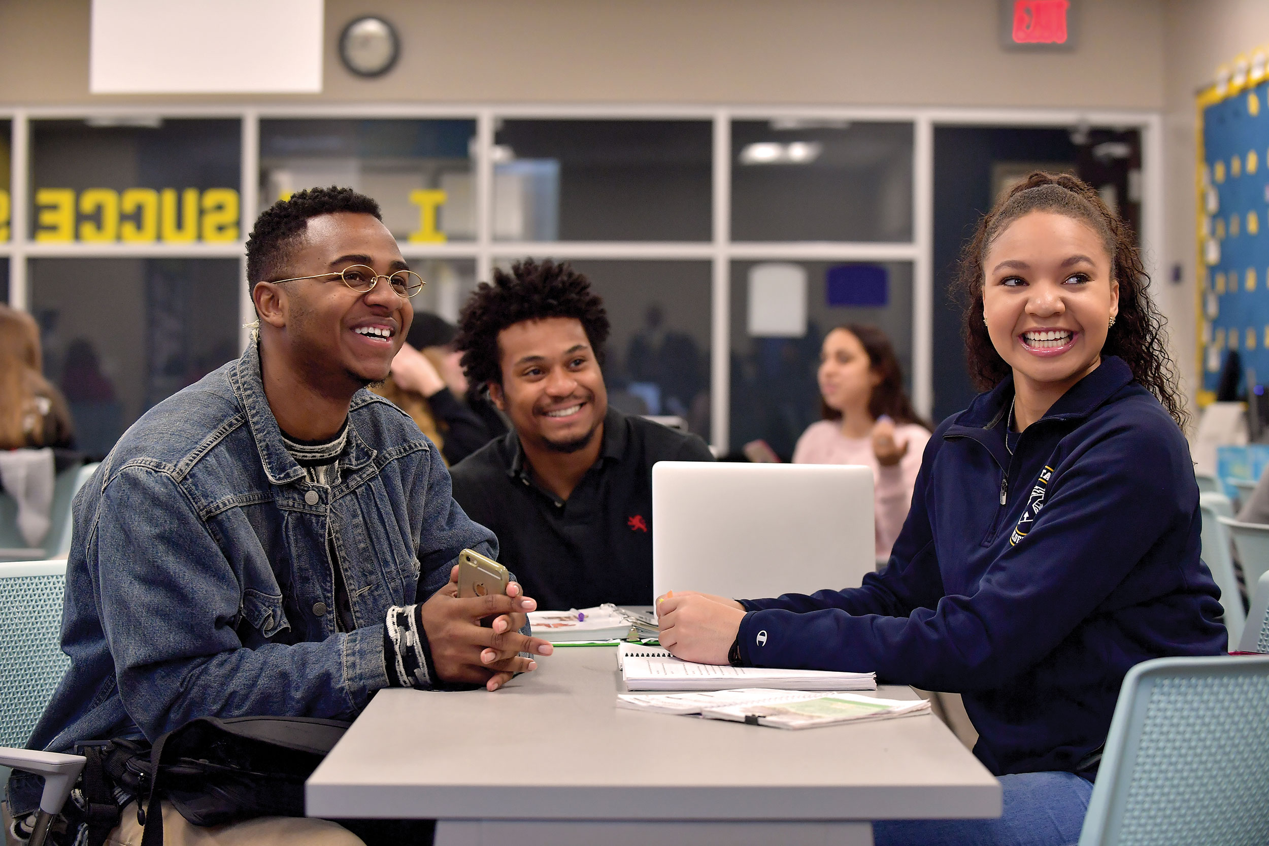 Photo of students, smiling and sitting around a desk with a laptop, looking at the front of the room