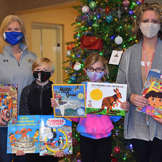 Showing some of the books donated to Beaver Local elementary students were (from left) Debbie Riggs of Kent State, students Brody Nign and Payton Smith, and Mrs. Brianne Hall