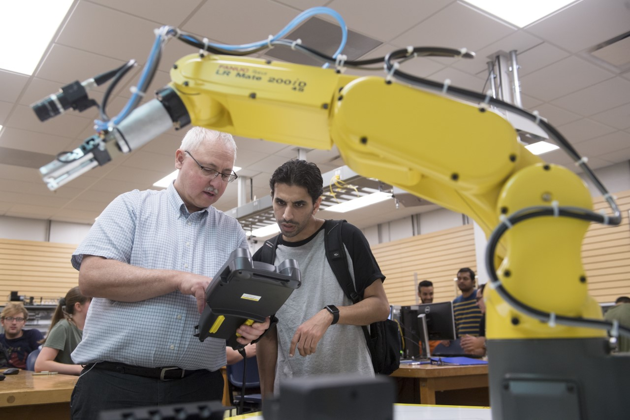 Darwin Boyd, Ph.D., works with a student in the robotics lab. (Photo taken prior to the COVID-19 pandemic)