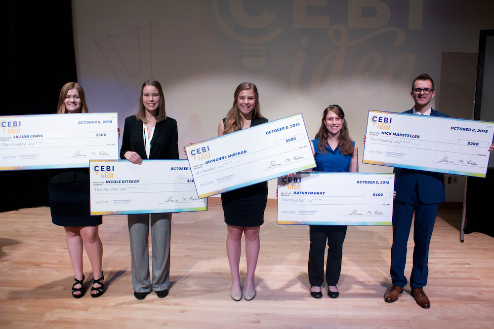 Students holding checks at a pitch competition