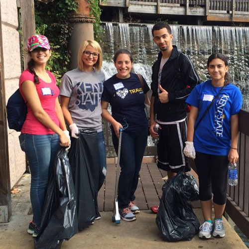 A group of students pose with trash bags after cleaning up trash in downtown Kent, Ohio.