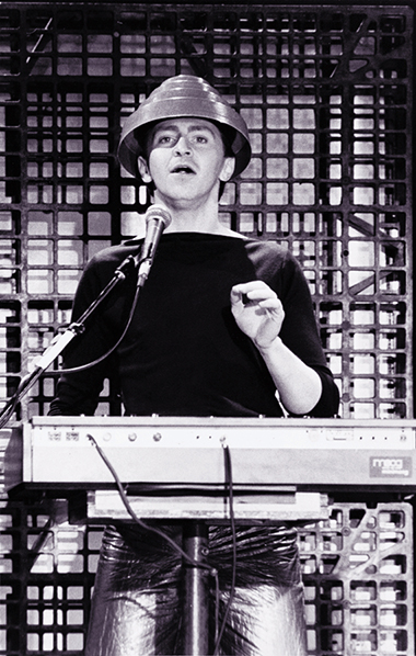 Jerry Casale on stage with his band Devo, standing in front of keyboard with microphone wearing red energy dome