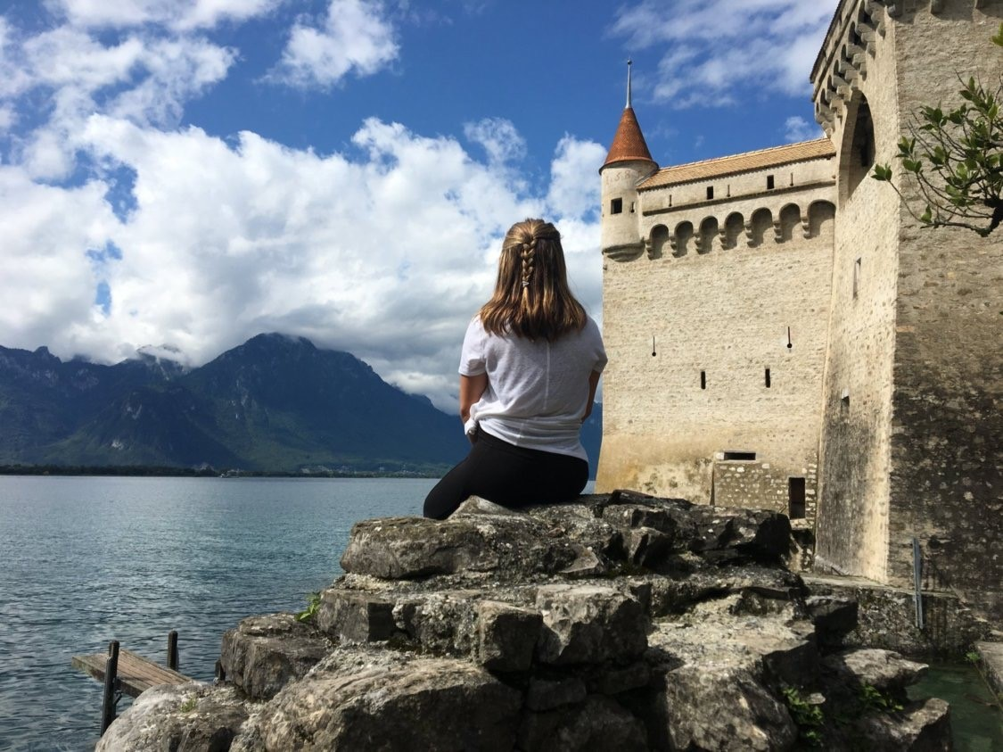 Student in Switzerland sitting next to a castle overlooking a lake.