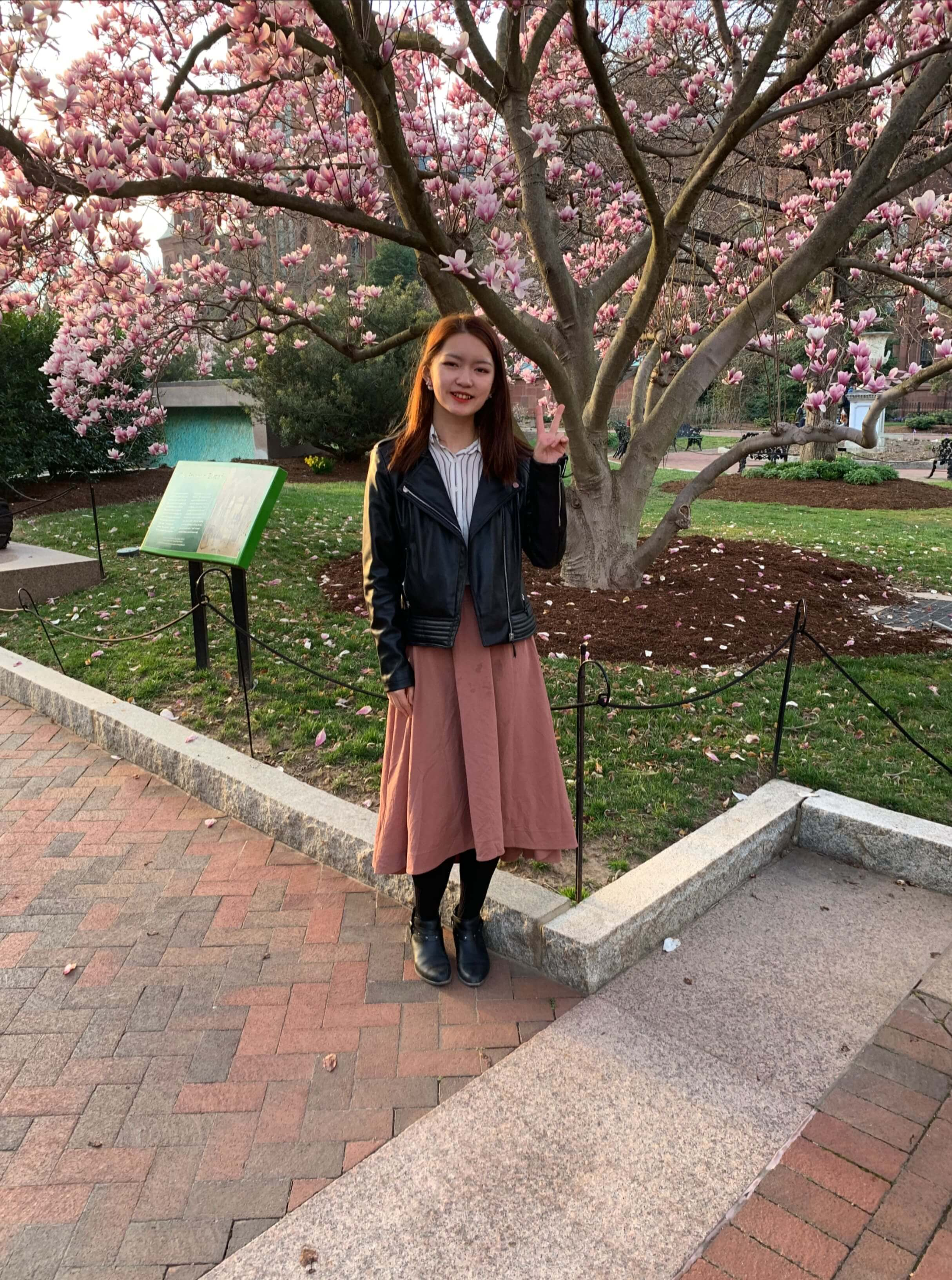 student in front of cherry blossom tree