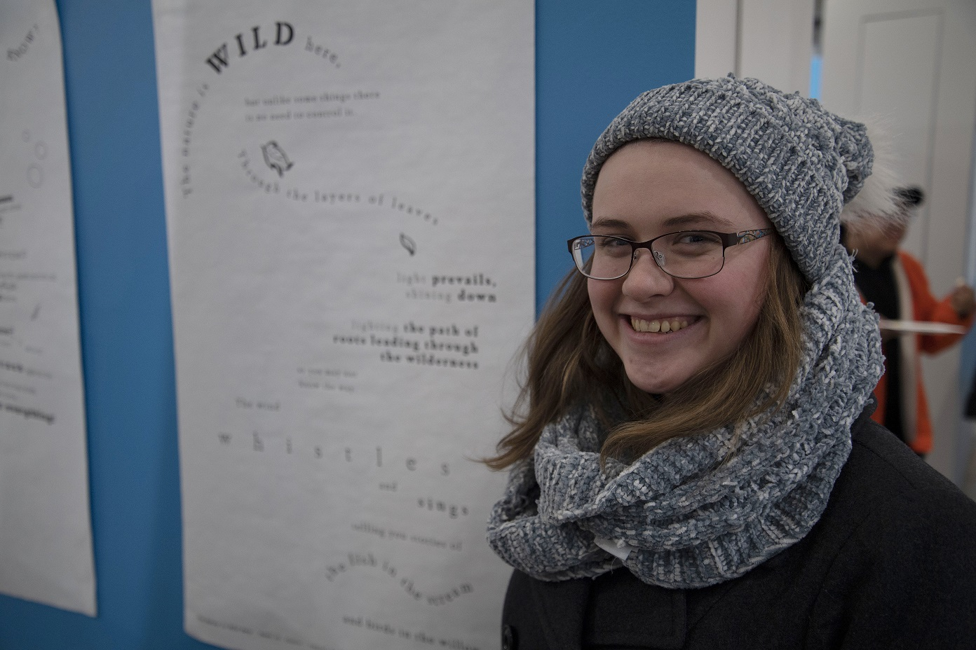 A VCD student stands next to her design at the Concrete Poetry Gallery Opening
