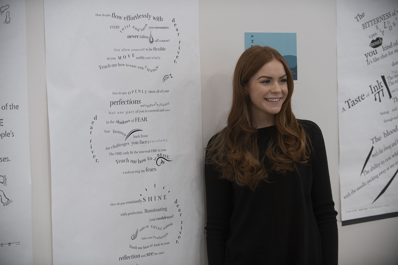 Student stands with design at Concrete Poetry Gallery Opening