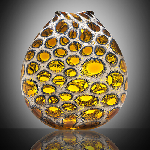 Glass work by Dan Alexander, a round vase with gold colored bubbles