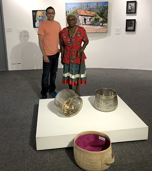 Davin Ebanks with Marlena Anglin, another award winning artist, who's silver thatch ground basket formed the inspiration and mold for his glass installation.