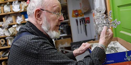 Artist Don Drumm in his studio holding a piece of metalwork.