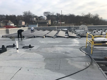 Crews begin assembling the solar panels on the rooftop of Kent State's Purinton Hall in East Liverpool.