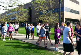 """Participants in last year's """"Race into Finals"""" 5K race and one-mile fun run/walk gather outside Henderson Hall for the start of the race."""