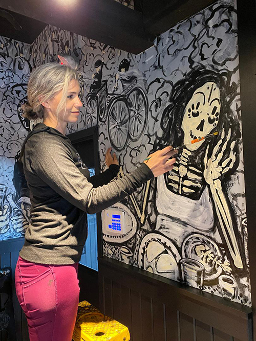 Eileen Dorsey painting an indoor mural of a skeleton for the restaurant Barrio