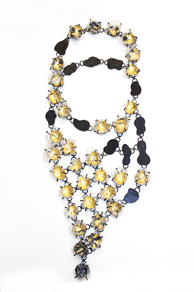 A necklace made of gold and black prong-set pieces by student Felicia Severn