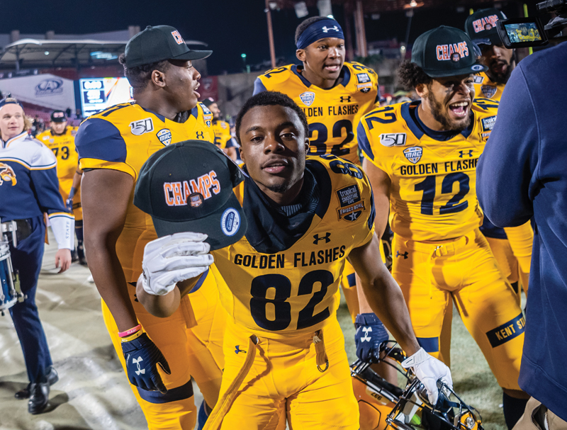A Kent State football player with a champion hat after winning the Frisco bowl.