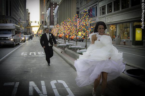 Photo of a bride and groom running down a city street by Georgio Sabino III