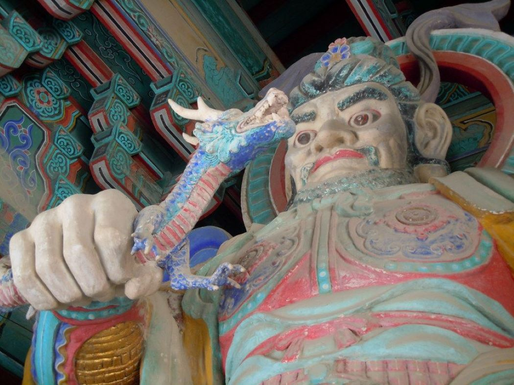 Statue of a temple guard with a dragon in hand at Gyeongju Bulguksa Temple in South Korea.