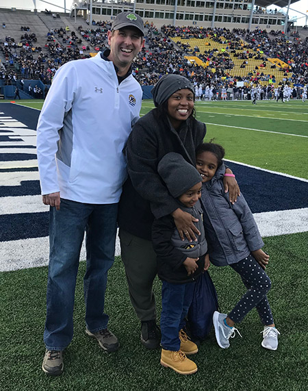 Ted McKown, associate director of admissions, is pictured with residence hall custodial employee Zipporah Cole and her children, Miah, 7, and Maximus, 5.