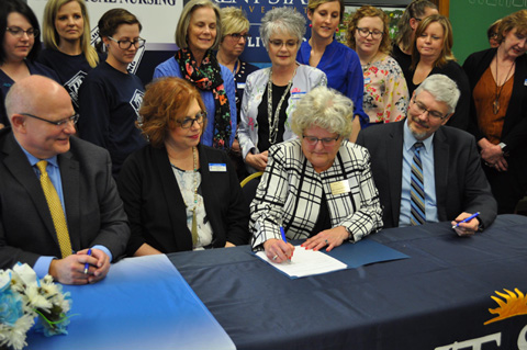 Dr. Carol Hrusovsky, program director for the ADN program at Kent State East Liverpool signs the ceremonial agreement form.