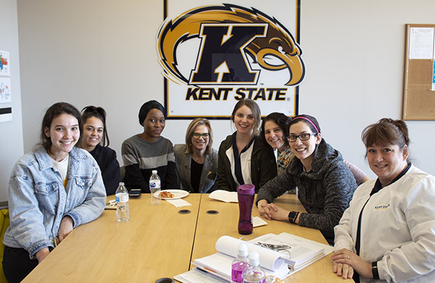 Students and dean posed and smiling in conference room