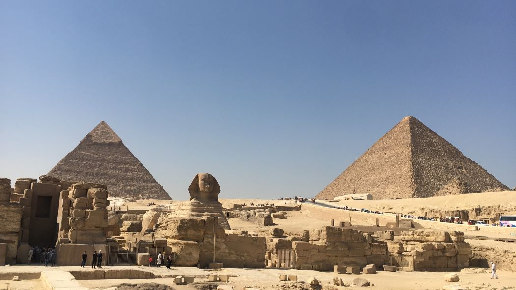 Great Sphinx of Giza with two pyramids in the background.