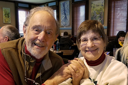 Jay and Joanie Solomon, holding hands smiling for the camera