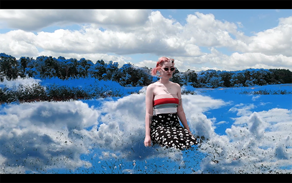 A still from Kate Rossello's video A World Without Men. Depicts a person in the middle of a field with sky and clouds projected on the grass.