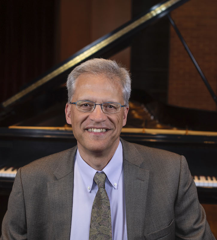 Kent McWilliams headshot in Ludwig Recital Recital in front of Steinway grand piano