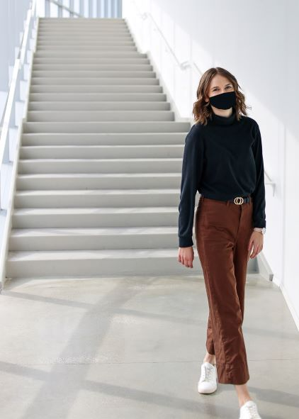 Elizabeth wearing a mask in the stairwell of the College of Architecture and Environmental Design building.