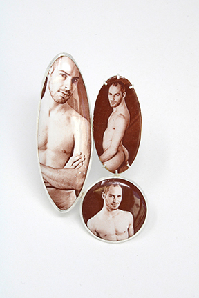 An enamel brooch by Andrew Kuebeck - three sepia images of a nude man in ovals.