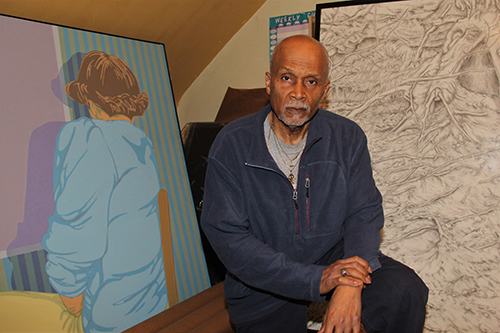 Lawrence Baker in front of his artwork