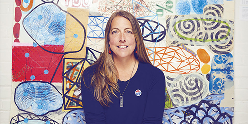 Portrait of Liz Maugans in front of her artwork.