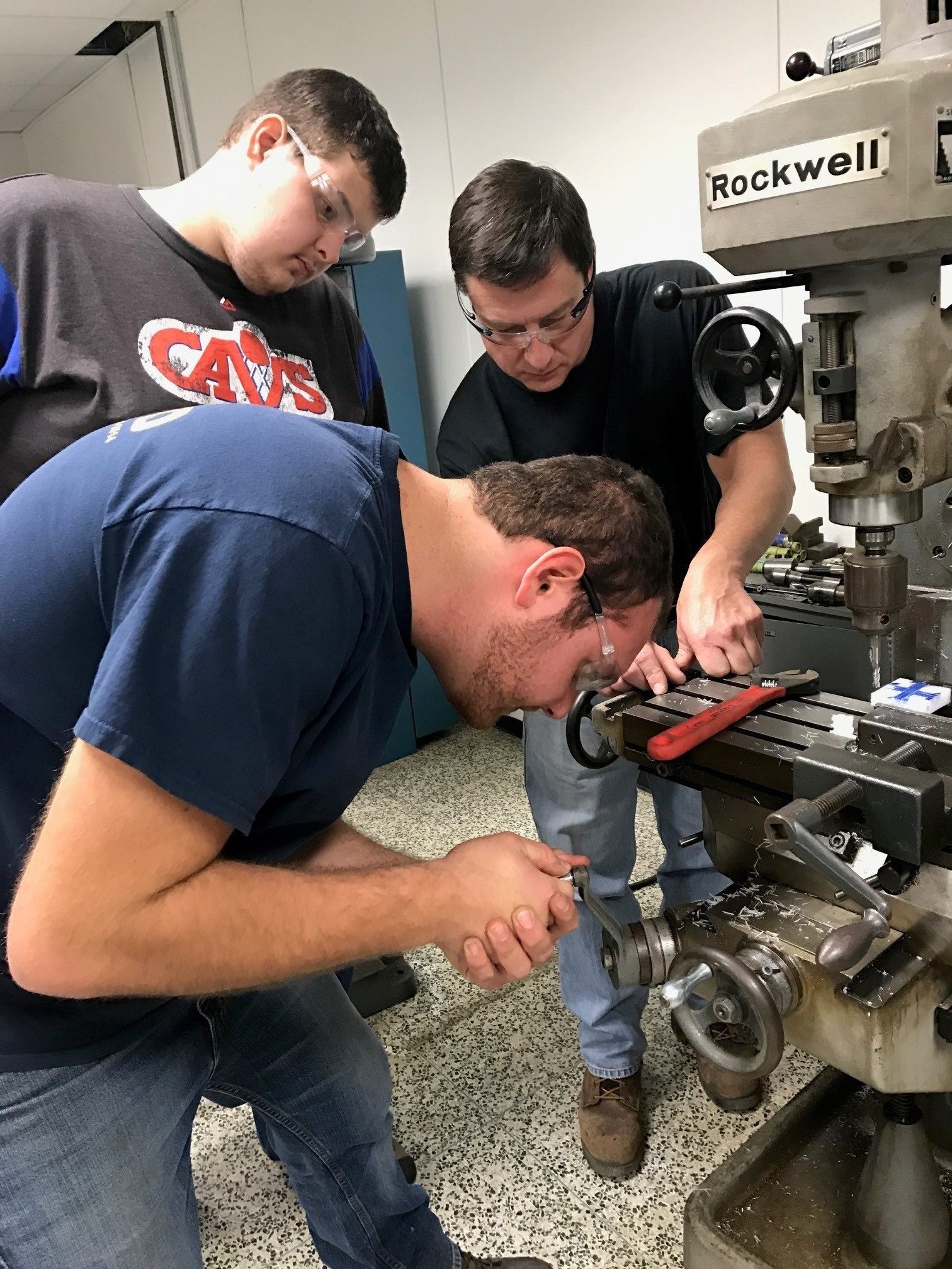 Mechanical Engineering Technology students working with faculty in the machine shop