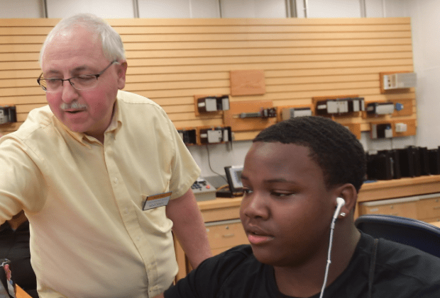 Staff helps a student out with their computer